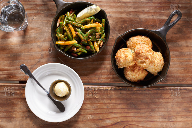 Overhead shot of sauteed green beans in a cast iron skillet with a slice of lemon, accompanied by cheese biscuits in another small cast iron skillet, on a small plate sits a pat of honey butter.