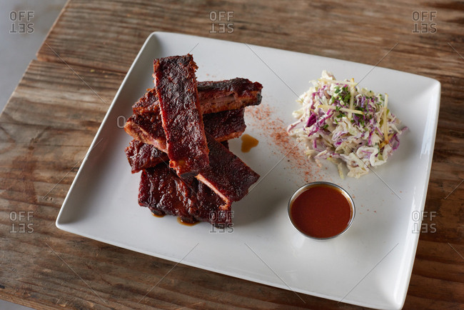 Plate of ribs rubbed with spices and slow smoked, cut into chunks and presented in stack served with a side of barbecue sauce and a side of coleslaw with cabbage and apples piled nearby on the white square plate.