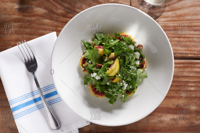 A salad of Tiger Stripe Figs, Arugula and goat cheese tossed in a simple vinaigrette, served in a white bowl.