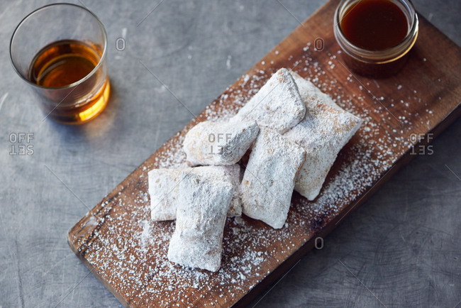 A thick wooden board holds a half dozen small beignets, with a small jar of bourbon caramel sauce in the back, with a glass of bourbon straight up sits nearby.