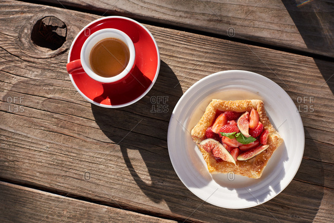Espresso in a red cup sits with a hexagon shaped pastry with chopped figs and strawberries, on a wooden table in the morning sun.