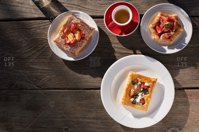 A single espresso with various pastries including two sweet fruit pastries of apricot and strawberries and fig and strawberries and another savory pastry with tomatoes, zucchini and feta cheese on a rustic wooden table in the morning sun.