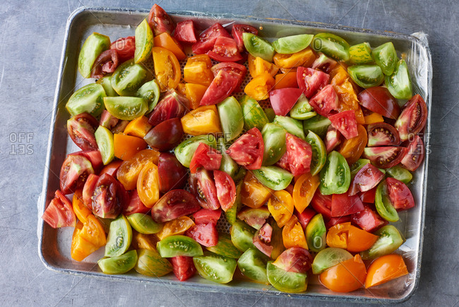 Chopped heirloom tomatoes on a large tray ready to be used in a salad in a farm to table restaurant