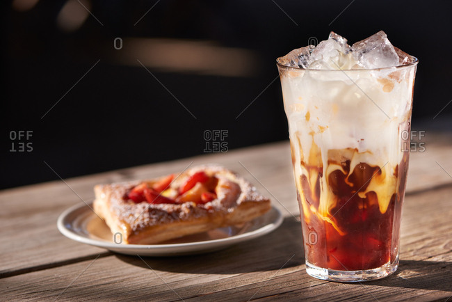 Ice coffee in a large pint glass, the recently poured in cream mixing in to the coffee, a sweet pastry of strawberries and apricots in the background.
