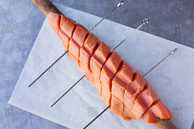 King salmon filet cut into portions and being prepared to be cooked on a pole outdoors.