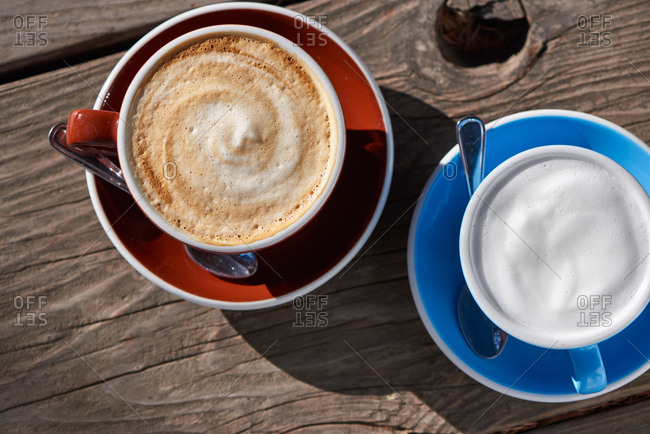 Latte in a blue cup and cappuccino in a brown cup on a wooden table in the morning sun.