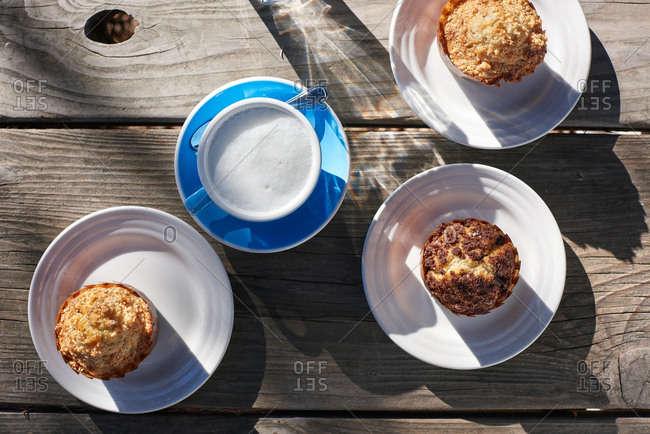 One latte and three muffins photographed from above on a wooden table in the morning light.