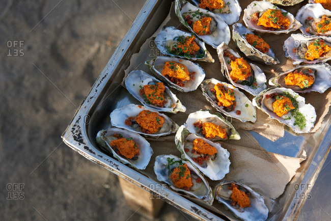 Oysters prepped in a large hotel pan with compound butter, chopped bacon and chives, ready to be grilled outdoors.