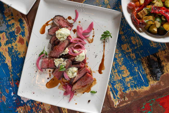Sliced tri tip steak presented on a square plate with pickled red onion, parsley and blue cheese, on a colorful surface at a catered event.