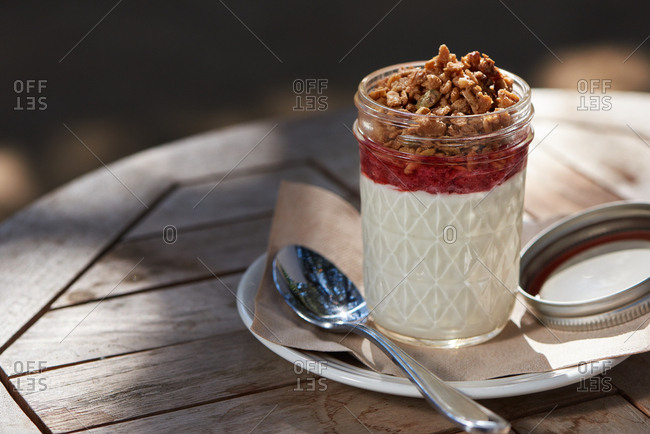 Granola and yogurt with strawberry jam in a small jar at an outdoor cafe for breakfast in the morning light.