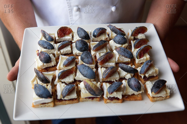 Plate of appetizers for an outdoor event, showing a small piece of crostini, fig jam, slice of brie and a slice of fresh fig on top, held by a chef.