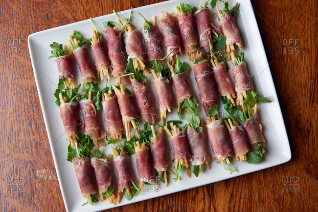 Prosciutto wrapped appetizers of matchstick apples and arugula presented on a plate for a catering event.