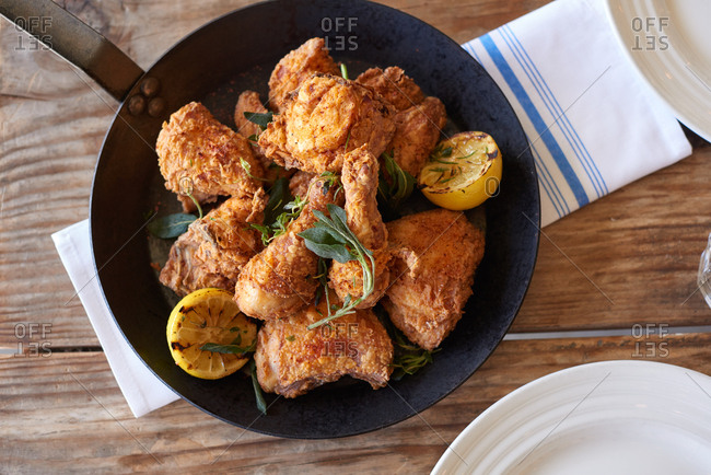 Fried chicken portions including drumsticks and breast portions presented in an iron skillet on a cloth bistro napkin on a wooden table.