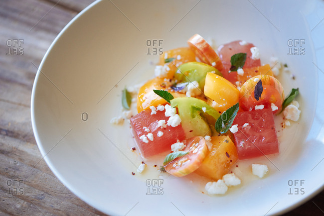 A heirloom tomato salad with feta cheese, watermelon and mint, drizzled with olive oil and presented in a shallow white bowl at a farm to table restaurant.