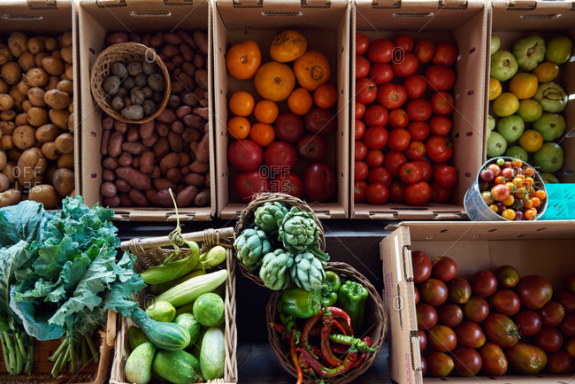 Various farmers market vegetables displayed in boxes, including various types of heirloom tomatoes, artichokes, collard greens, peppers, green and hot portugal, red potatoes, white potatoes, and purple potatoes.