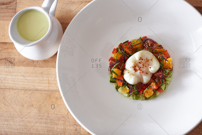 A small arrangement of cucumbers, citrus, heirloom tomato, basil strips, poblano peppers holding an olive oil poached egg with dried red pepper on top.