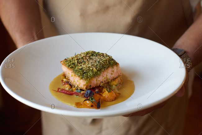 Chef holding a plate of elegant food including a pan-fried salmon with basil breadcrumbs, over a squash curry puree, heirloom cherry tomatoes and baby eggplant.