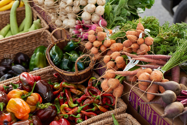 Abundance of produce at an outdoor farmer's market featuring Parisian carrots, peppers and various radishes, displayed for sale at an outdoor farmer's market.