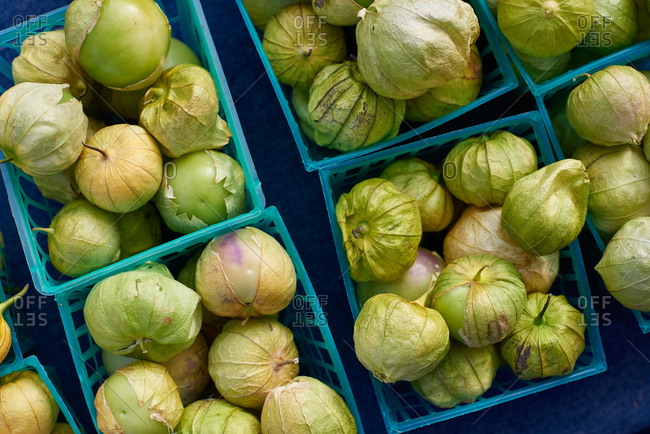 Tomatillos separated into various small baskets for sale at an outdoor farmer's market photographed from above.