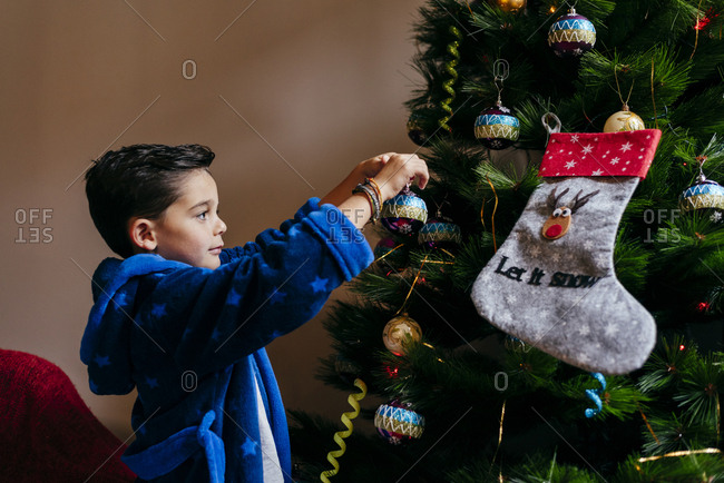 Cute caucasian kid putting the ball on the Christmas tree