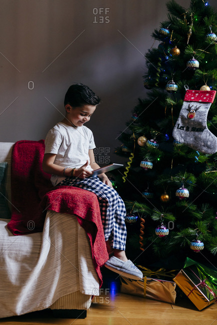 Handsome caucasian kid sitting on the couch using the tablet near to a christmas tree