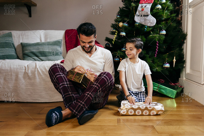 Caucasian father and son opening gifts near to the Christmas tree