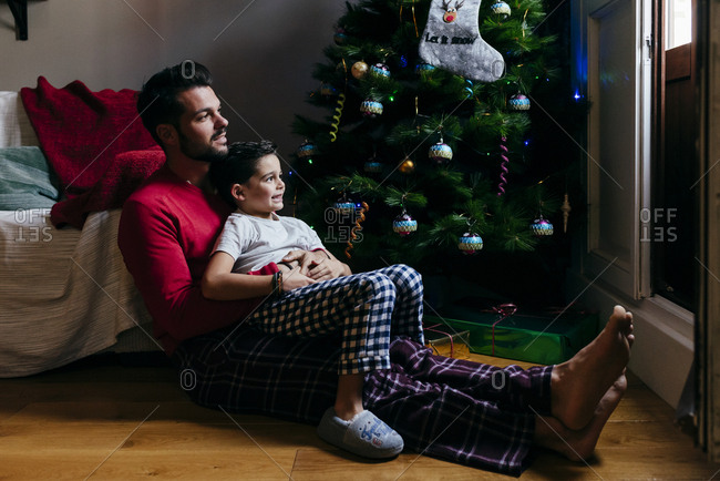 Father and son sitting on the floor at home near to the Christmas tree