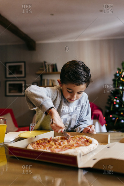 Cute caucasian kid cutting pizza at home at Christmas