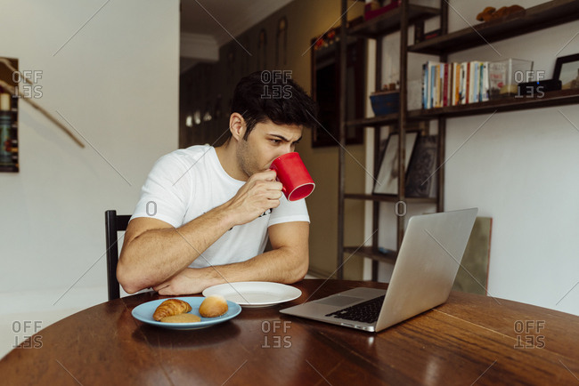 Handsome caucasian man having breakfast at home with laptop on the table