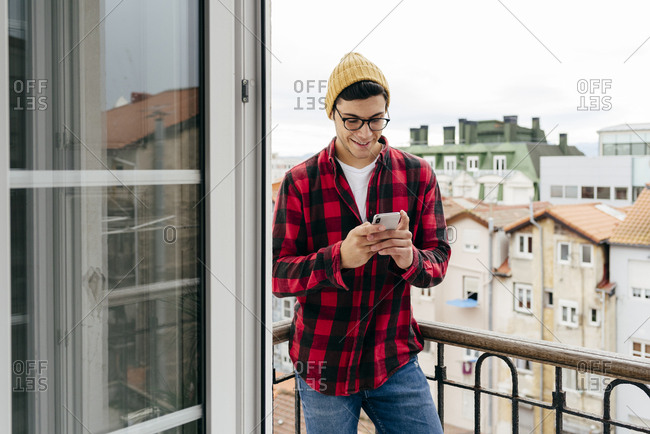 Trendy caucasian man with wool cap and plaid shirt using the phone on the balcony at home