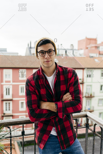 Portrait of trendy caucasian man with wool cap and plaid shirt on the balcony at home