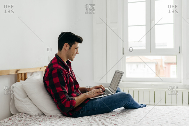 Handsome caucasian man working on the laptop in bedroom at home