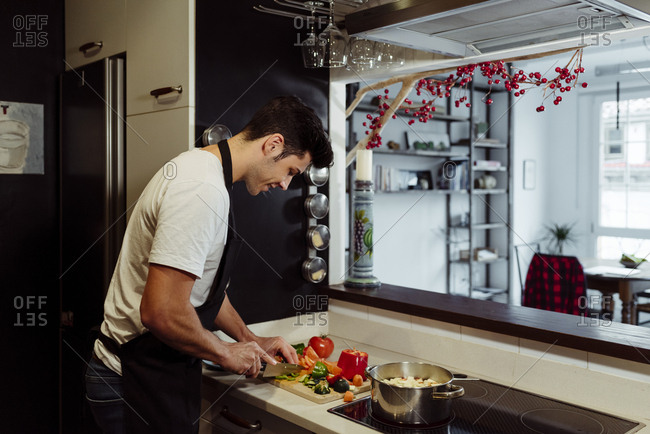 Handsome caucasian young man with apron cutting vegetables in the kitchen at home