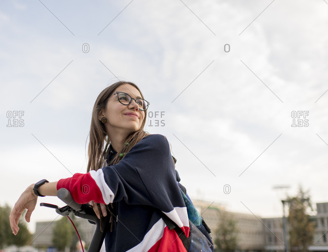 Millennial woman riding scooter - Offset
