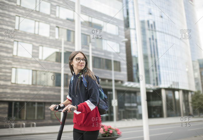 Millennial woman riding scooter in the city