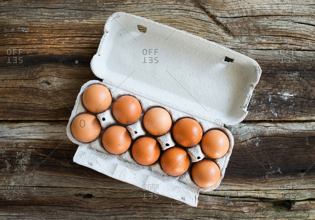 Overhead view of fresh eggs on a wooden table