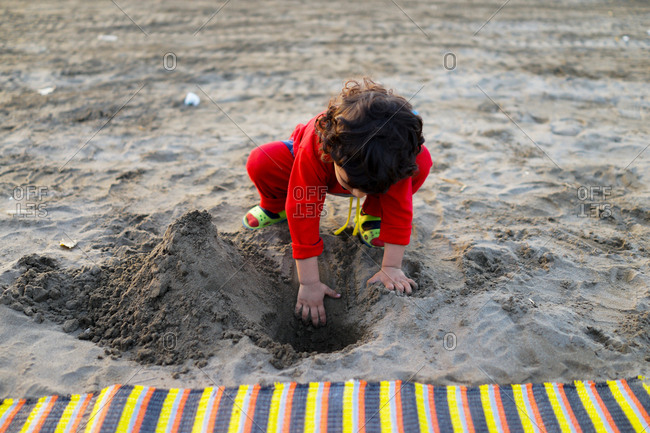 Little girl playing in the sand at the seaside