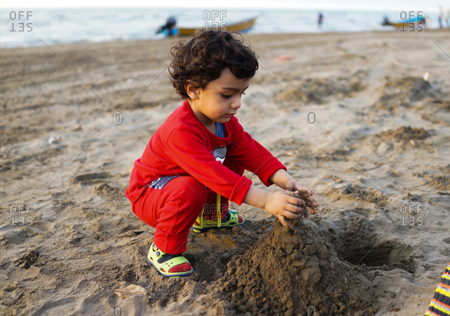 Young girl building sandcastle