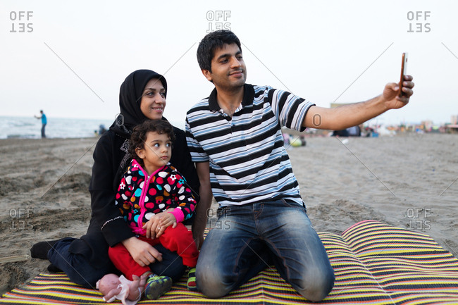 Muslim family taking selfie on the beach