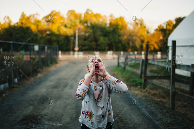 Tween girl yodeling on a country lane