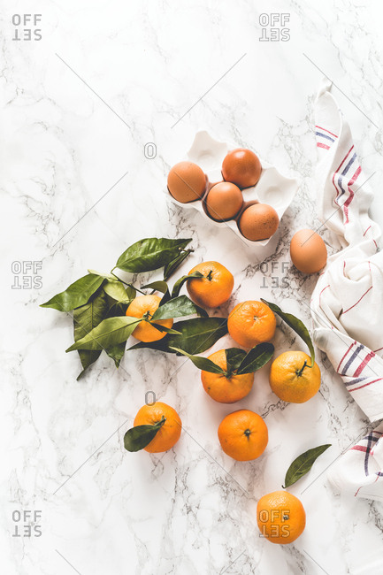 Fresh clementines with green leaves on light background