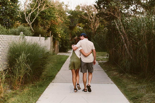 Couple hugging and walking down a sidewalk together