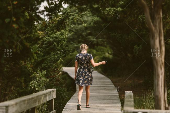 Woman walking down a tree-lined boardwalk
