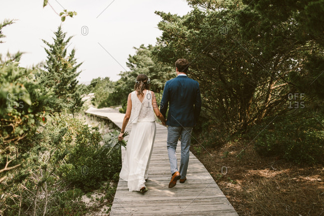 Bride and groom holding hands and walking down a tree lined boardwalk