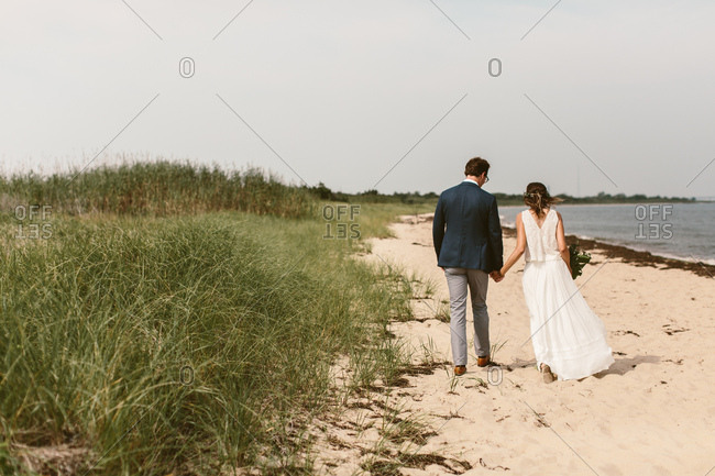 Bride and groom holding hands and walking down an east coast beach