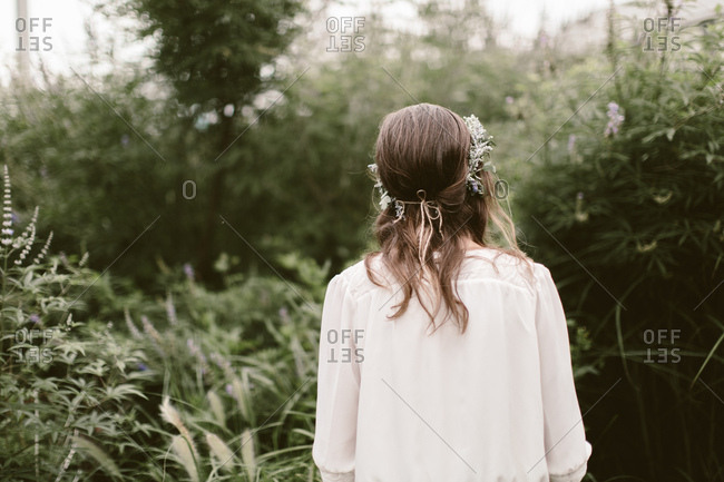 Woman with flower crown wandering through overgrown garden