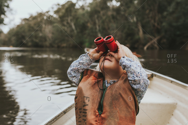 Young girl sits in a boat with red binoculars looking up to discover birds in the trees.