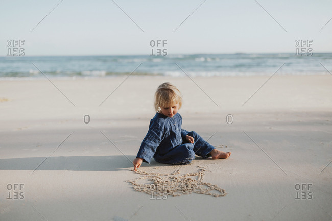 Young blonde girl quietly draws in the sand at an Australian white sandy beach.
