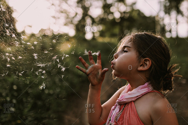 A girl blows dandelion seeds from a dandelion flower into the air with sun behind her.