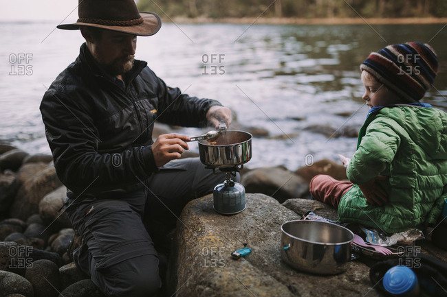 A father and son prepare a simple camp meal by the sea with their puffer jackets and beanie on after a long hike in the forest.